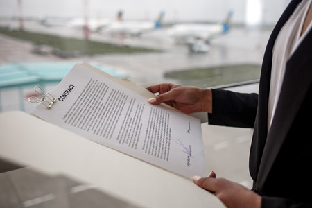 Attentive to all details. Woman in official clothes is standing near window in airport building and holding folder with contract. Aerodrome with aircrafts in background. Close-up