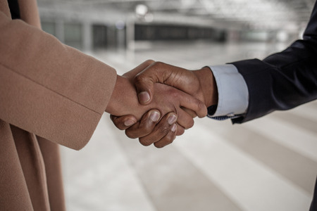 Friendship. Close-up of strong handshake of confident businesspeople. Male and female are greeting each other