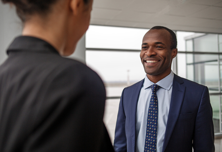 Happy to see you. Portrait of successful young qualified african businessman is standing with his partner female at light office. He is looking at her with joy. Back view of woman Imagens - 94128871