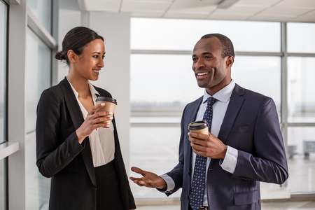Conversationalist. Cheerful elegant young business partners are standing in office and enjoying espresso. They are having pleasant communication. Man is gesticulating while saying something with smile