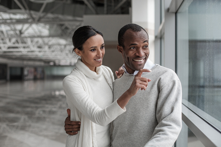 What wonderful view. Portrait of cheerful happy couple are standing together at station hall. Woman is pointing finger forward while husband is hugging her. They are looking aside with curious
