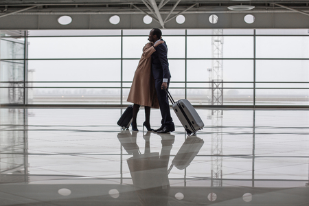 Full length of charming businesswoman and businessman are greeting each other at terminal lounge. They are standing with suitcases and hugging Stok Fotoğraf