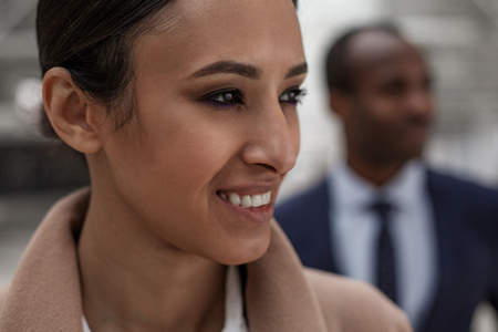 Confident glance. Close-up of face of gorgeous charming young woman is looking aside with smile. She is standing with african man in background. Selective focus