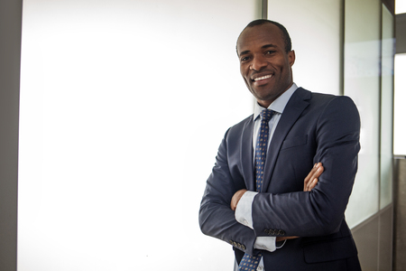 Happy glance. Waist up portrait of cheerful young elegant african entrepreneur in suit is looking at camera with joy. He is standing in office with arms crossed. Copy space in the left side