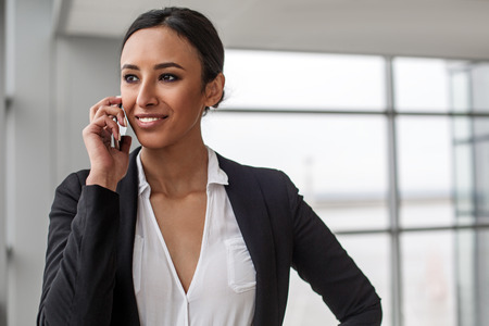 Pleasant communication. Portrait of attractive charming businesswoman is standing in office. She is enjoying conversation on mobile phone while looking aside with wide smile. Copy space Stok Fotoğraf