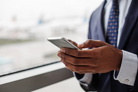 Helpful device. Close-up of hands with smartphone. Young african businessman wearing official clothes is using modern gadget. Copy space in the left side
