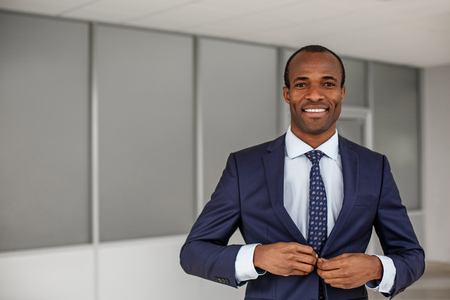 Going to meeting. Waist up portrait of cheerful elegant young african businessman in formal clothes is standing in indoors and looking at camera with wide smile while buttoning his jacket. Copy space