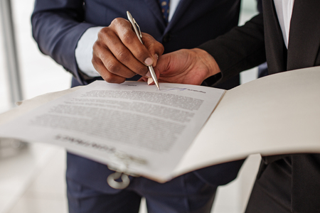 Sign it here. Woman is standing in office and holding folder with contract while man in suit is signing it. Close up of hand with pan. Selective focus Reklamní fotografie