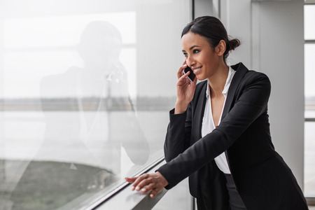 Involved in communication. Cheerful elegant gorgeous businesswoman is standing in office while leaning on window. She is talking on smartphone while looking through glass with smile. Copy space Foto de archivo