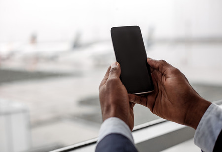 Useful device. Close up of screen of mobile phone in hands of african man. He is holding gadget against window. Copy space in the left side Stock Photo