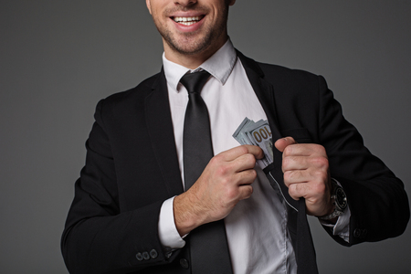 Happy unshaven male taking cash from modern suit. Budget and career concept. Isolated Stock fotó