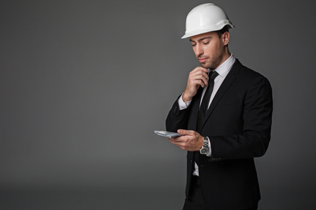 How can I spend it. Portrait of pensive builder looking at money. Profit concept. Copy space and isolated