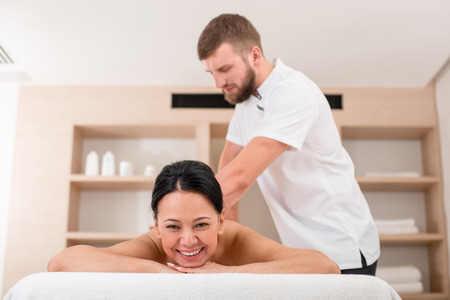 Young masseur giving glad asian woman a massage. Relaxed lady smiling and lying on the couch in beauty salon