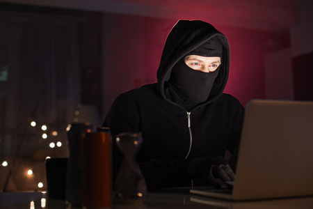 Portrait of calm computer burglar typing in laptop in apartment at night. Criminal and technology concept Stok Fotoğraf