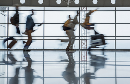 Travel concept. Blurred terminal lounge with running tourists. Man is pushing airport trolley with luggage and woman who is sitting on it. Full length Фото со стока