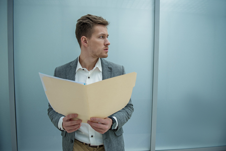 Work papers. Young man is holding documents while standing in office. He is looking aside seriously. Copy space in the right side