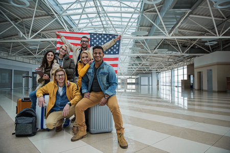 We love our country. Full length portrait of optimistic young friends are sitting on suitcases at airport with usa flag. They are looking at camera with smile while expressing happiness. Copy space Stok Fotoğraf