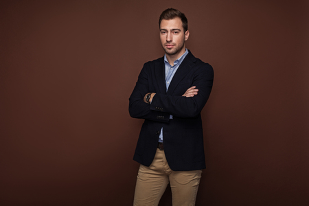 Portrait of calm unshaven male with crossing arms. Business and style concept. Isolated and copy space