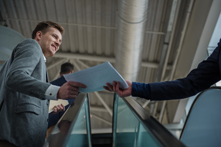Your papers. Low angle of stylish positive man is rising on moving staircase. He is taking documents from his colleague with smile. Selective focus