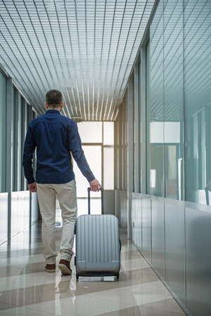 Active lifestyle. Full length back view of elegant traveler is walking along airport hallway with his suitcase