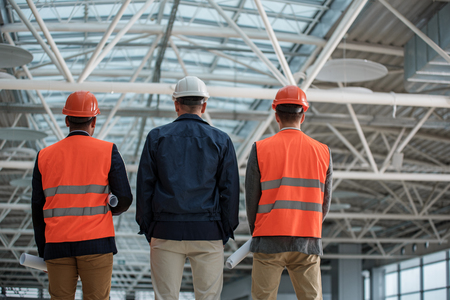 Low angle of qualified engineers in safety-helmets are standing at construction area. They are looking at their project while holding blueprints. Back view Imagens