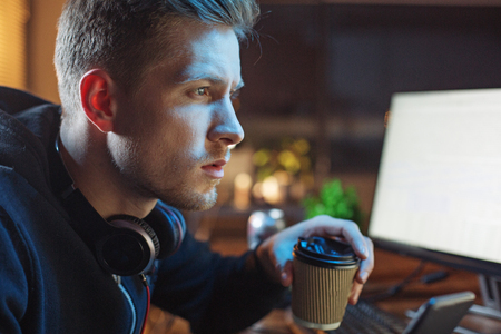 Serious unshaven male tasting cup of coffee while working with computer at table. Occupation concept