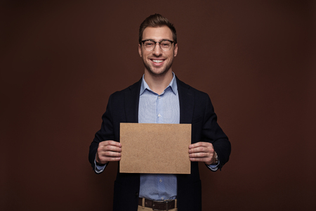 Portrait of cheerful bearded male holding carton board in hand. Advertisement concept. Isolated