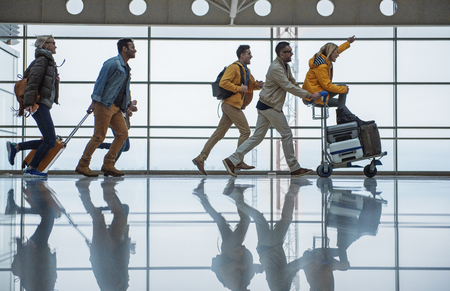 Do not want to be late. Full length profile of joyful young friends are running along terminal hall with suitcases. Male is pushing airport trolley with luggage and female who is sitting on it Zdjęcie Seryjne