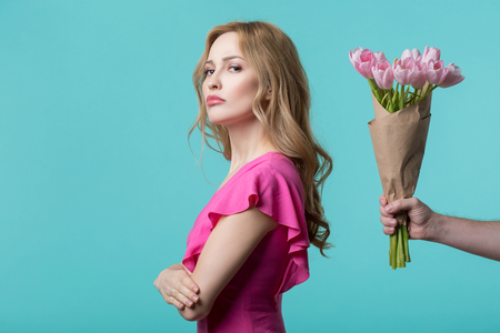 Abused young woman is turning back to male hand holding flowers. Apology concept. Isolated and copy space Stock Photo