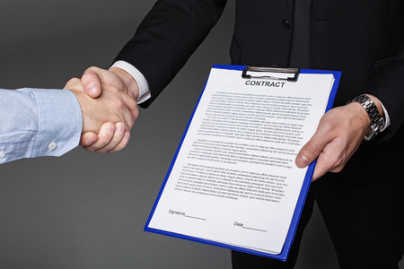Close up businessman hand concluding contract while keeping it. He shaking colleague hand. Bargain concept