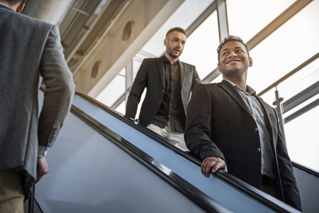 Low angle of young males are on moving staircase inside of building. Selective focus of cheerful man with wide smile is standing and looking aside with joy