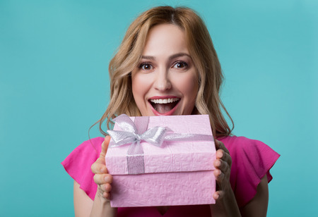 Portrait of happy young lady holding pink gift box and laughing. She is looking at camera with excitement. Isolated Фото со стока