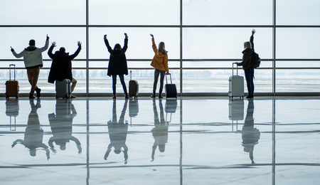 Hello. Full length back view of passengers are looking through the glass wall and waving arm to someone. They are standing at terminal lounge with luggage