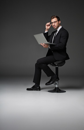 Full length portrait of serene unshaven male noting in laptop while sitting on chair. He looking at camera. Labor concept