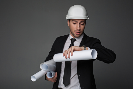 Hurry up. Portrait of uneasy bearded architect looking at watch while keeping different rolls of paper in hand. Construction concept. Isolated Stock fotó