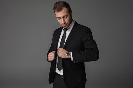 Portrait of calm businessman looking at watch. It locating on arm. Time and career concept. Isolated