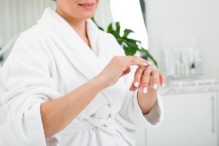 Senior smiling female putting cream on the hand with her finger. She is wearing bathrobe and having rest in beauty salon Archivio Fotografico