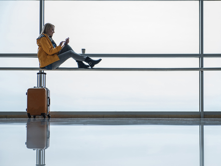 Always in touch. Full length of positive girl with luggage is looking at screen of mobile phone and texting messages. She is sitting on handrail and drinking coffee in modern airport. Copy space