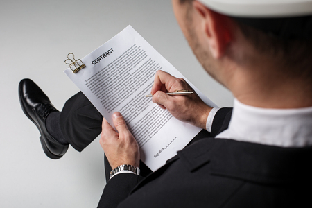 Top view close-up builder hand signing document. He looking through it. Business concept