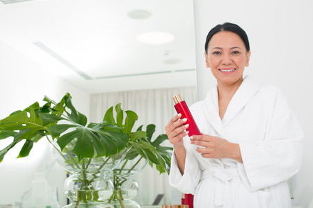Waist up portrait of pleased asian woman examining cosmetic product in wellness center. She is looking at camera. Copy space in left side