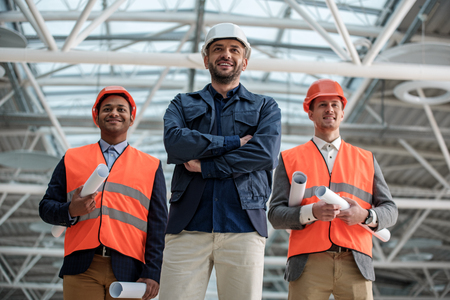 Professional team. Low angle portrait of joyful young builders are standing together and looking ahead with smile while holding blueprints. They are wearing safety-helmets