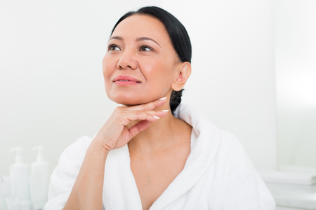 Portrait of quiet mature lady relaxing in beauty salon. She is putting cream on her chin with smile