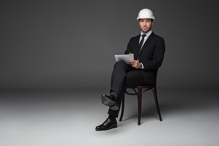 Full length portrait of serious architect working with paper while sitting at chair. Job concept. Copy space