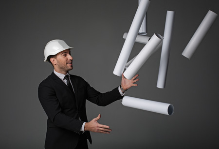 Side view smiling unshaven builder juggling different projects. He gesticulating arms. Profession concept. Isolated Stock Photo