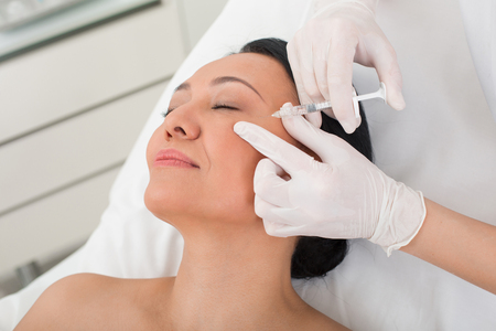 Calm adult female going for rejuvenating treatment in wellness center. She is lying in chair while taking procedure. Her eyes are closed Stock Photo