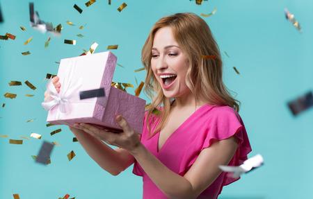 中に何があるか。好奇心旺盛な若い女性は、現在の箱を見て、幸せで笑っています。ホリデーのお祝いのコンセプト