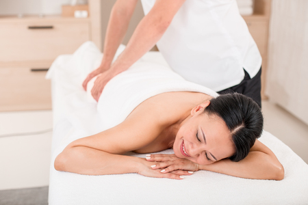 Pleased middle-aged lady getting a massage in wellness center. She is smiling with closed eyes and lying on massage table