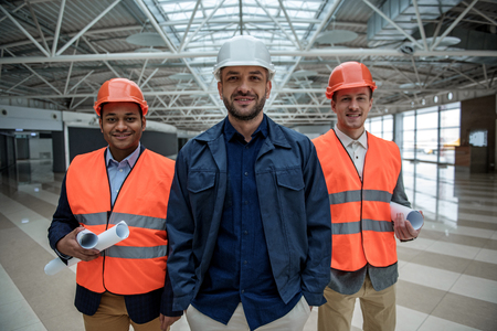 Professional team of builders. Portrait of positive pleasant qualified young architects are standing together and looking at camera with joy. They are wearing safety-helmets and holding blueprints