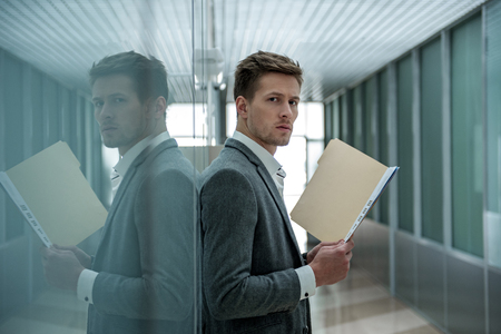 Bad results. Serious young stylish man is standing and holding documents while looking at camera confidently. He is reflected in wall Stok Fotoğraf