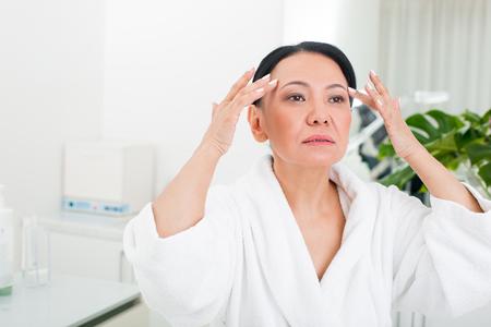 美容院で休んでいる静かな先輩女性の肖像。彼女は真剣な表情で指で顔のしわに触れている 写真素材 - 94515859